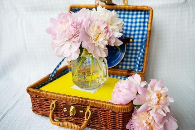 Bardzo piękny bukiet różowych piwonii stoi w wazonie na drewnianej walizce. Premium Zdjęcia