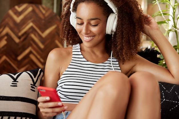 Bardzo Się Cieszę, że Ciemnoskóra Kobieta Udostępnia Multimedia W Sieciach Społecznościowych, Czuje Się Komfortowo Na Sofie, Rozmawia Przez Telefon Komórkowy, Połączony Z Internetem. Zrelaksowany Afroamerykanin Lubi Rekreację Darmowe Zdjęcia