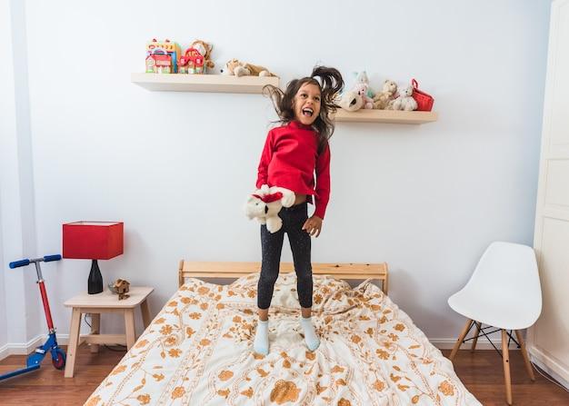 Bardzo Szczęśliwa Mała Dziewczynka W Czerwonym Swetrze T-shirt Z Długą Szyją, Skoki Na łóżku. Premium Zdjęcia
