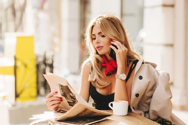 Bardzo Zajęta Pani Pozuje W Restauracji Na świeżym Powietrzu Z Gazetą, Czytając Ją Z Zainteresowaniem Na Rozmycie Tła Darmowe Zdjęcia