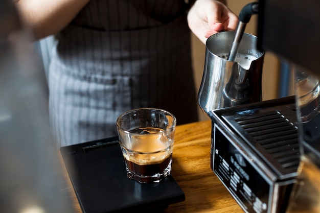 Barista ręcznie gotuje mleko do robienia kawy latte w kawiarni� Darmowe Zdjęcia