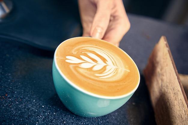 Barista Serwująca Kawę W Kawiarni. Kobieta Daje Latte Lub Cappuchino Klientowi Za Kontuarem. Restauracja Coffee Shop Concept. Stonowane Zdjęcie. Skopiuj Miejsce świeżo Parzona Kawa Premium Zdjęcia