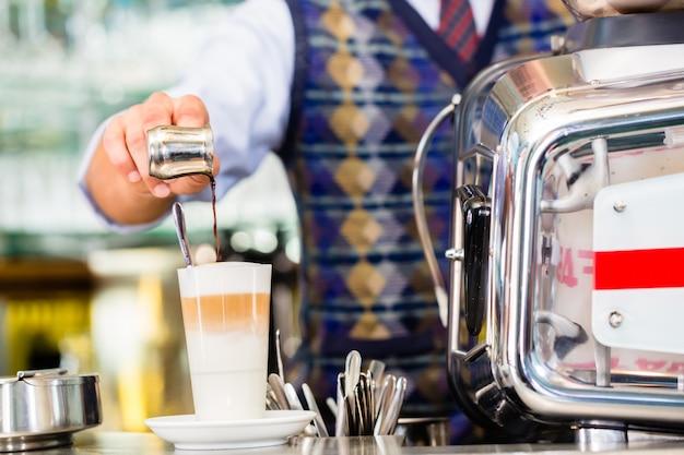 Barista w cukiernianej dolewanie kawie espresso strzelał w latte macchiato Premium Zdjęcia