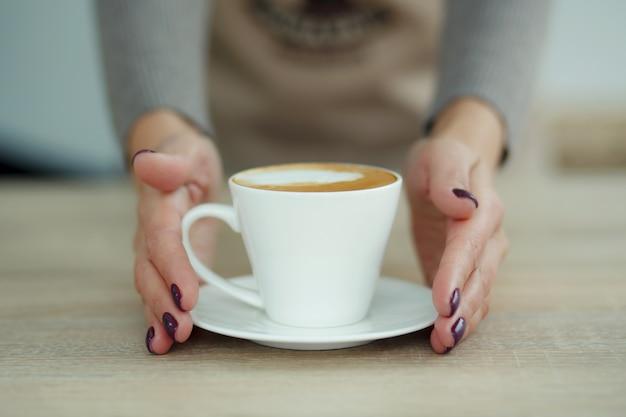 Barista w fartuchu w kawiarni daje świeżo parzoną świeżą kawę klientowi Premium Zdjęcia