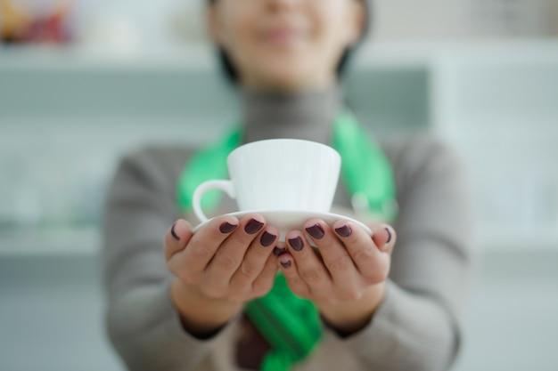 Barista w fartuchu w kawiarni podaje klientowi świeżo parzoną świeżą kawę Premium Zdjęcia