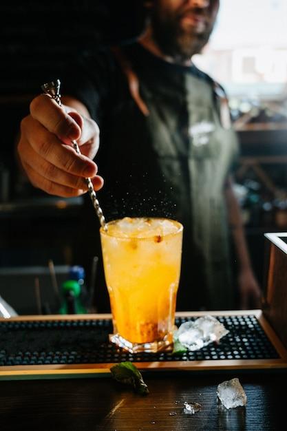 Barman miesza słodki i świeży pomarańczowy letni koktajl w szklance Premium Zdjęcia