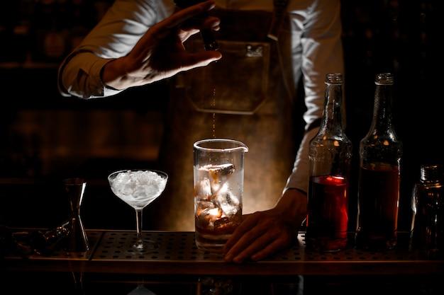 Barman Nalewa Esencję Z Małej Szklanej Butelki Premium Zdjęcia