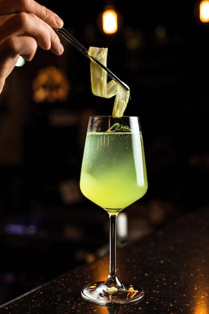 Barman Przygotowuje Koktajl, Dodaje Seler Do Kieliszka Wina Z Mrożonym Napojem W Kolorze Zielonym Premium Zdjęcia