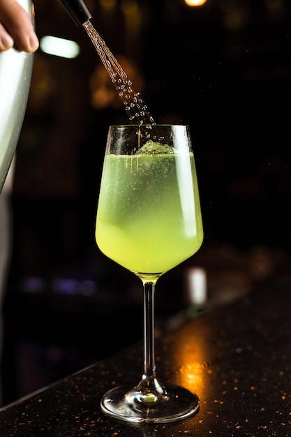 Barman Przygotowuje Zielony Koktajl Z Lodem W Kieliszku Wina, Dodając Wodę Sodową Premium Zdjęcia