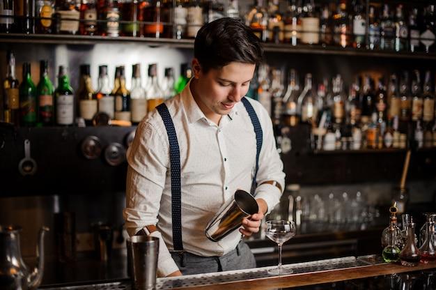 Barman W Białej Koszuli Robi Koktajl Przy Blacie Barowym Premium Zdjęcia