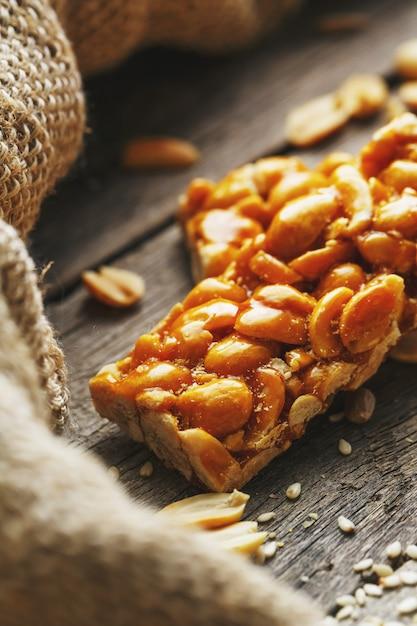 Batonik z orzeszkami ziemnymi. pyszne orientalne słodycze gozinaki z nasion słonecznika, sezamu i orzeszków ziemnych, pokryte miodem z błyszczącym lukrem Premium Zdjęcia
