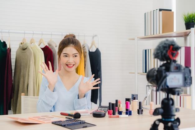 Beauty blogger przedstawia kosmetyki kosmetyczne siedząc w przedniej kamery do nagrywania wideo Darmowe Zdjęcia