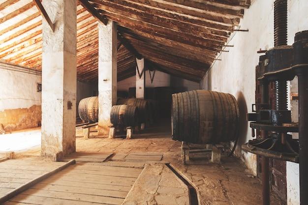 Beczki Czerwonego Wina Ułożone W Starej Piwnicy Winnicy W Hiszpanii, Alicante Premium Zdjęcia