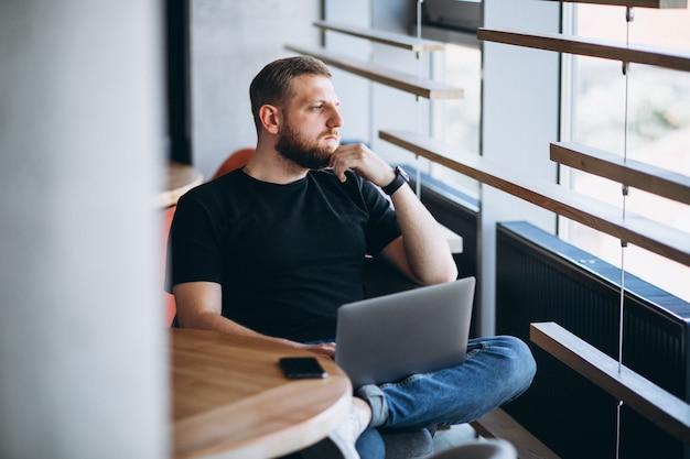 Beraded mężczyzna pracuje na laptopie w kawiarni Darmowe Zdjęcia
