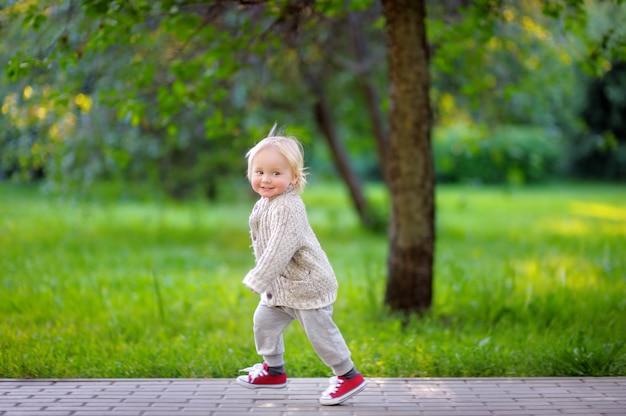 Berbeć Chłopiec Biega W Parku Przy Wiosną Lub Letnim Dniem Premium Zdjęcia
