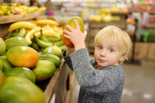 Berbeć Chłopiec W Sklepie Spożywczym Lub Supermarkecie Wybiera świeżego Organicznie Mango Premium Zdjęcia