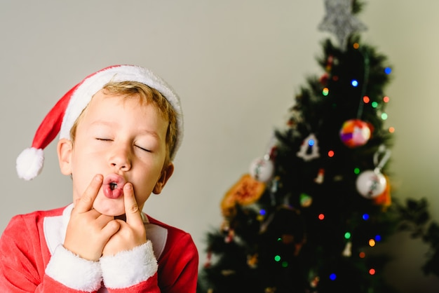 Berbeć Z święty Mikołaj Kostiumem Robi Twarzom Obok Choinki, Boże Narodzenie Wakacje Pojęcie. Premium Zdjęcia