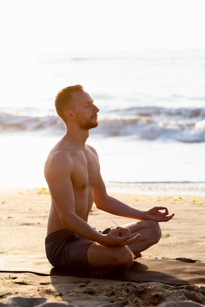 Bez Koszuli Mężczyzna Medytuje Na Plaży Darmowe Zdjęcia