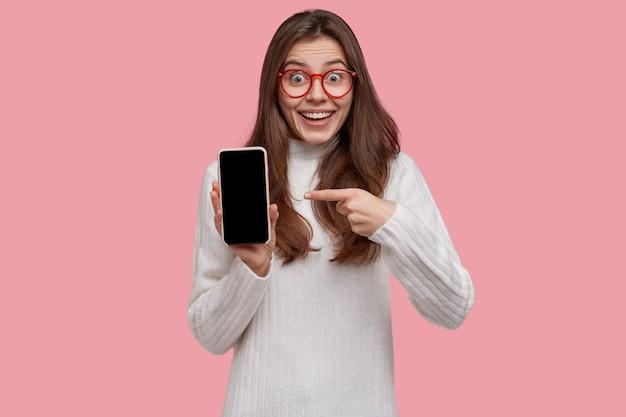 Bez Słowa Podekscytowana Młoda Kobieta Wskazuje Na Ekran Makiety Smartfona, Próbuje Pokazać Coś Niesamowitego, Nosi Biały Sweter Darmowe Zdjęcia