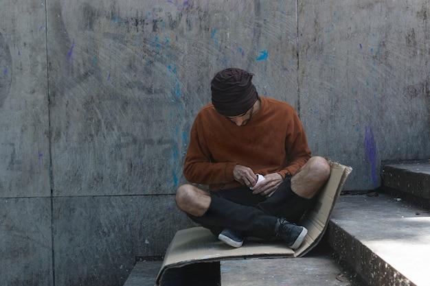 Bezdomny Mężczyzna Siedzi Na Tekturze Na Zewnątrz Darmowe Zdjęcia