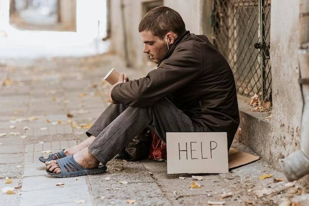 Bezdomny Na Ulicy Z Filiżanką I Znak Pomocy Darmowe Zdjęcia