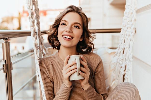 Beztroska Dziewczyna Z Brązowym Makijażem Picia Herbaty Na Balkonie. Zdjęcie Przyjemnej Brunetki Kobiety W Sukience Z Dzianiny Ciesząc Się Kawą. Darmowe Zdjęcia