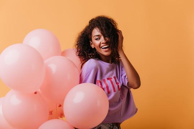 Beztroska Młoda Dama Trzyma Balony Z Helem Na Pomarańczowo I Uśmiecha Się. śmiejąca Się Pozytywna Czarna Dziewczyna Obchodzi Urodziny. Darmowe Zdjęcia