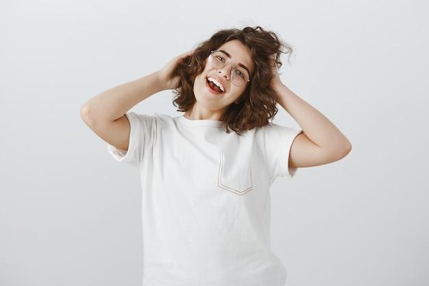 Beztroska Szczęśliwa Kobieta W Okularach Dotyka Jej Nowej Fryzury Z Zadowoloną Miną Darmowe Zdjęcia