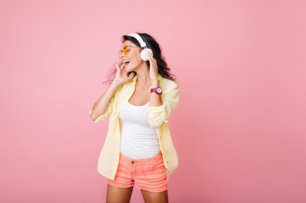 Beztroski Hiszpanin Kobieta W Różowe Szorty śpiewa Podczas Pozowania. Wewnątrz Portret Modnej Azjatyckiej Dziewczyny W Białych Słuchawkach Bez Rękawów Toucnhing I Rozglądając Się. Darmowe Zdjęcia