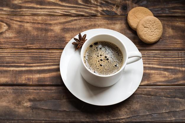 Biała Czapka Z Kawą I Anyżem Na Małym Talerzu Z Dwoma Ciastkami Premium Zdjęcia