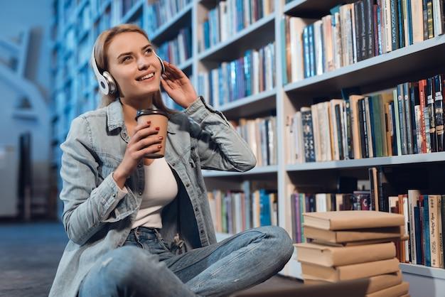 Biała Dziewczyna Blisko Półka Na Książki W Bibliotece. Student Słucha Muzyki. Premium Zdjęcia