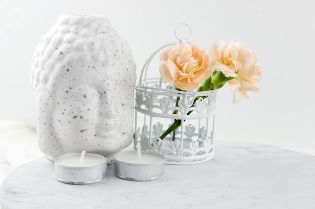 Biała figurka ceramiczna głowa buddy, ozdobna klatka z kwiatami i świecami Premium Zdjęcia