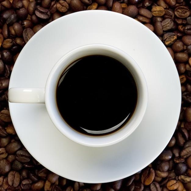 Biała Filiżanka Czarnej Kawy Na Powierzchni Ziaren Kawy Darmowe Zdjęcia