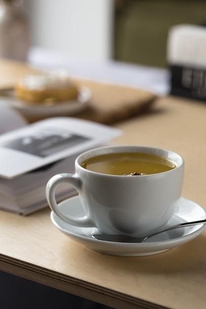 Biała filiżanka herbaty i książka na stole w kawiarni. Premium Zdjęcia