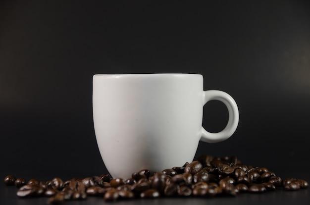 Biała Filiżanka Z Kawowymi Fasolami Na Czarnym Tle Premium Zdjęcia