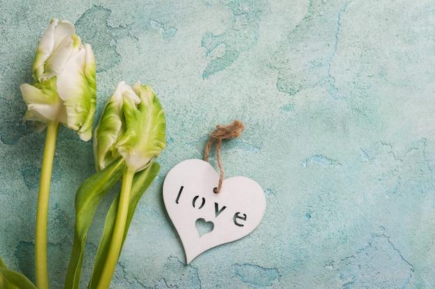 Biała i zielona tulipanowa para z drewnianym sercem Premium Zdjęcia