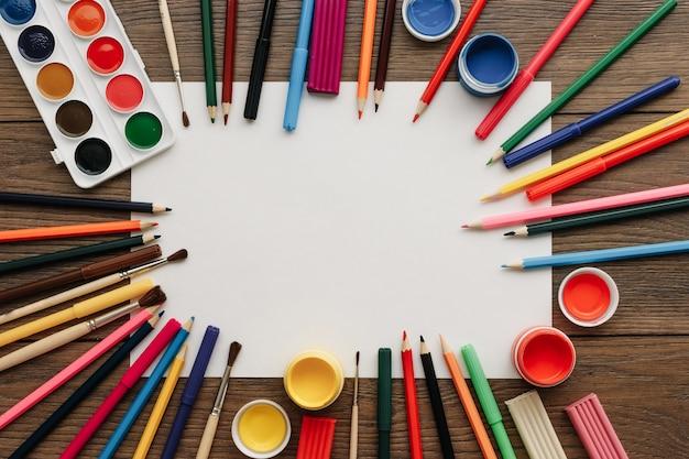 Biała kartka papieru a4 leży na drewnianej brązowej ramie stołu obok farb, pędzli, kolorowych ołówków. Premium Zdjęcia