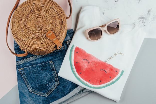 Biała koszulka, niebieskie jeansowe spodenki, modna organiczna torba rattanowa, okulary przeciwsłoneczne Premium Zdjęcia