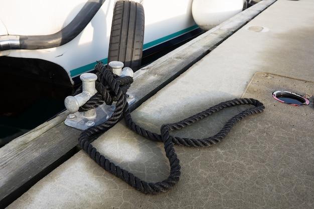 Biała łódź Przywiązana Do Molo Czarną Liną Premium Zdjęcia