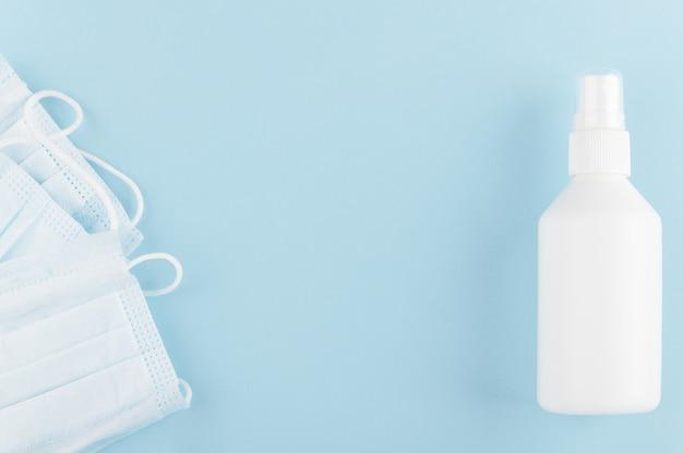 Biała Niemarkowa Butelka środka Dezynfekującego I Medycznej Maski Ochronnej Na Stole. Covid-19 I Kwarantanna. Premium Zdjęcia