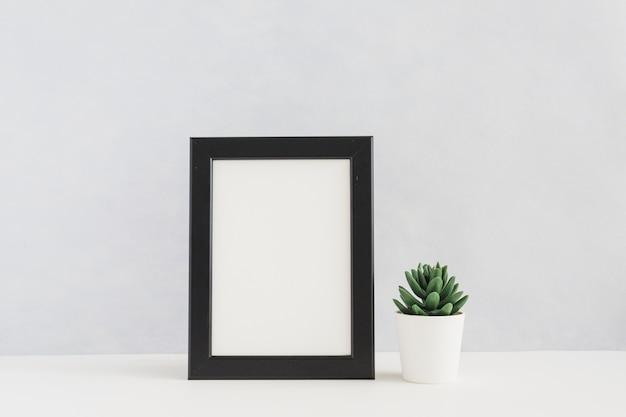 Biała obrazek rama i kaktusowy garnek na białym biurku przeciw ścianie Darmowe Zdjęcia
