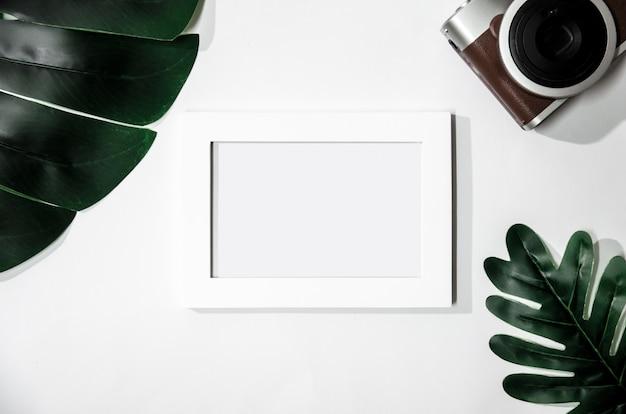 Biała Obrazek Rama Z Zielonymi Liśćmi I Kamera Na Bielu Odizolowywającym Premium Zdjęcia