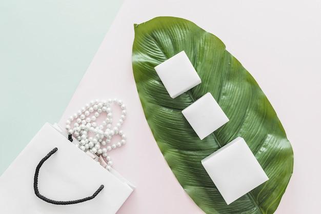 Biała Perła Naszyjnik Spada Z Torby Na Zakupy I Trzy Białe Pudełka Na Kolorowym Tle Darmowe Zdjęcia
