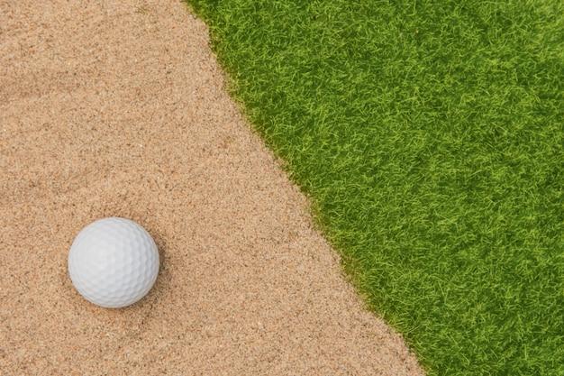 Biała piłka golfowa w bunkrze piasku na polu golfowym Premium Zdjęcia