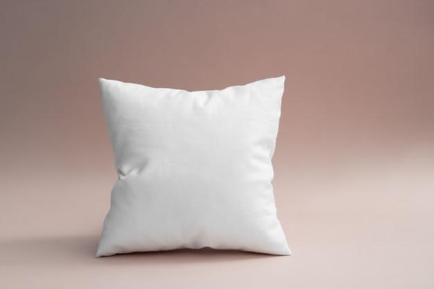 Biała poduszka na szaro-różowym tle. Premium Zdjęcia
