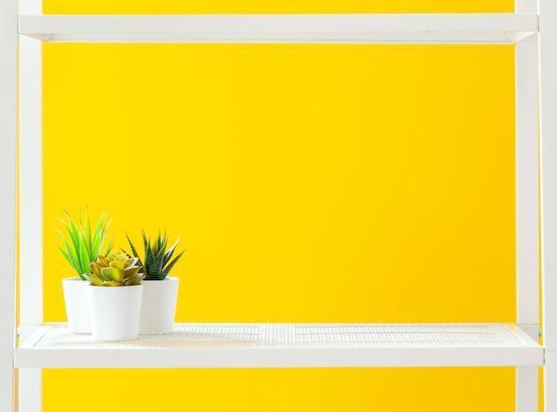 Biała półka z artykułami biurowymi na jasnożółtym Premium Zdjęcia