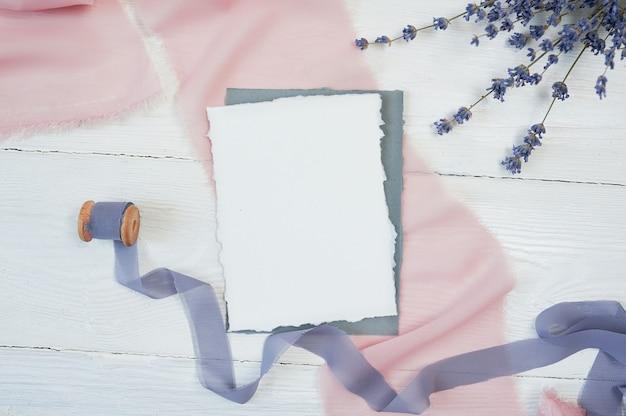 Biała pusta karta na tle różowa i błękitna tkanina z lawendowymi kwiatami Premium Zdjęcia