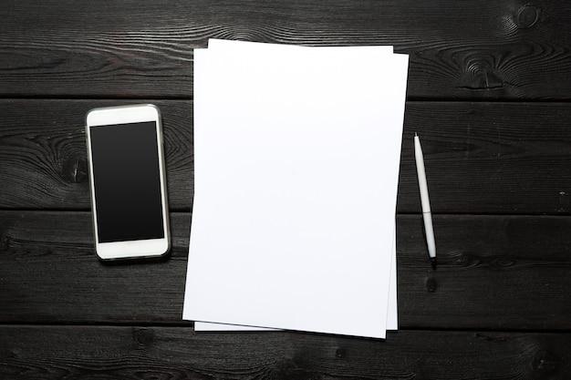 Biała wizytówka na drewnianym stole. pusty portret a4. Premium Zdjęcia