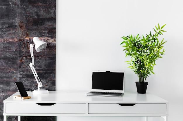 Białe biurko z laptopem i lampą Darmowe Zdjęcia