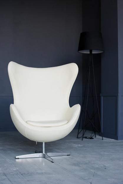 Białe designerskie krzesło we wnętrzu czarnego loftu studio Premium Zdjęcia